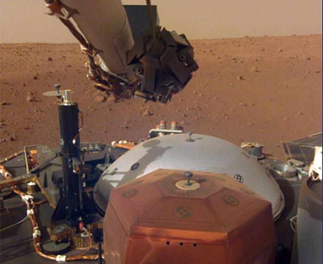 Blick der InSight-Bordkamera auf die eigenen Instrumente und den Mars-Horizont. Copyright: NASA
