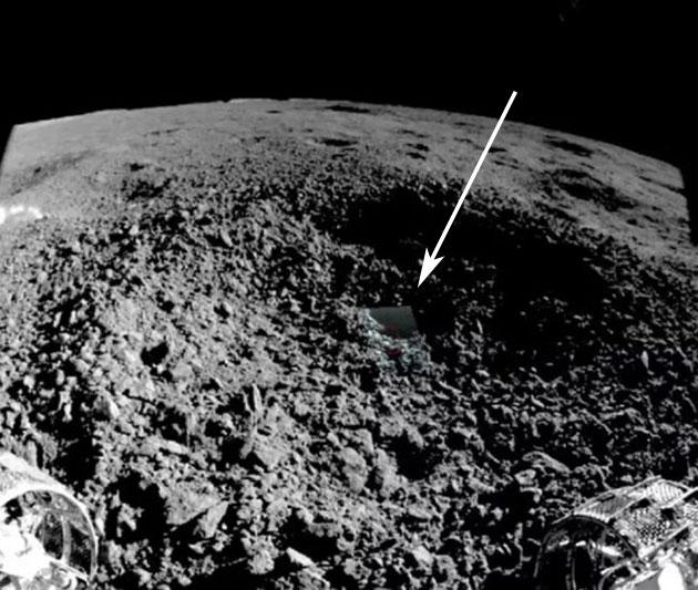 """Blick des Rovers auf die """"ungewöhnliche Substanz"""" im Innern eines Kraters auf der Rückseite des Mondes. Im Vordergrund sind die Fronträder des Rovers zu erkennen. Copyright: CNSA/CLEP"""