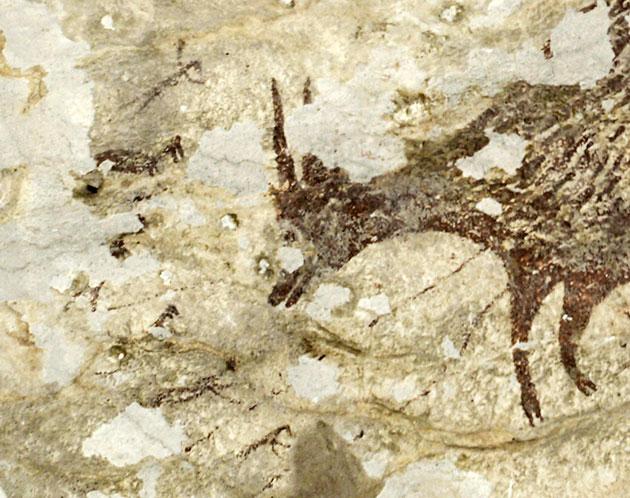 Kleine Mischwesen aus Tier und Mensch (l.) jagen einen Büffel. Felszeichnung aus einer Höhle auf Sulawesi. Copyright/Quelle: Endra / Griffith University