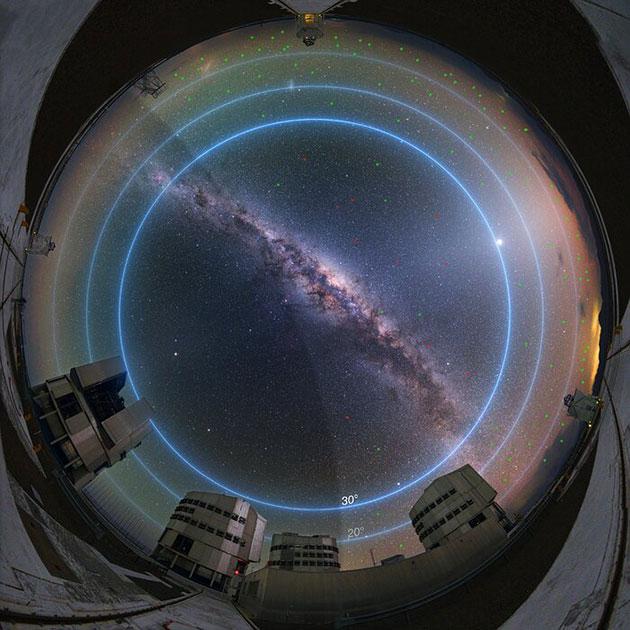 Dieses Bild zeigt den Nachthimmel am Paranal-Observatorium der ESO in der Dämmerung, etwa 90 Minuten vor Sonnenaufgang. Die blauen Linien markieren die Höhengrade über dem Horizont. Bis zu etwa 100 Satelliten könnten hell genug sein, um in der Dämmerung mit dem bloßen Auge sichtbar zu sein (Magnitude 5-6 oder heller). Die überwiegende Mehrheit von ihnen, deren Positionen mit kleinen grünen Kreisen im Bild markiert sind, würde tief am Himmel stehen, unter etwa 30 Grad Höhe, und/oder wäre eher schwach. Nur einige wenige Satelliten, deren Standorte rot markiert sind, würden sich über 30 Grad oberhalb des Horizonts befinden - dem Teil des Himmels, an dem die meisten astronomischen Beobachtungen stattfinden - und wären relativ hell (Magnitude von etwa 3-4). Zum Vergleich: Polaris, der Nordstern, hat eine Magnitude von 2, was 2,5 Mal heller ist als ein Objekt der Magnitude 3. Die Anzahl der sichtbaren Satelliten sinkt zur Mitte der Nacht hin ab, wenn mehr Satelliten in den Erdschatten fallen, was durch den dunklen Bereich links im Bild dargestellt wird. Die Satelliten im Erdschatten sind unsichtbar. (Klicken Sie auf die Bildmitte, um zu vergrößerten Varianten zu gelangen) Copyright: ESO/Y. Beletsky/L. Calçada