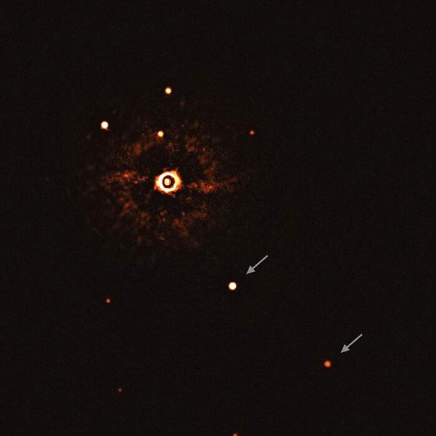 Die ESO-Aufnahme zeigt den Stern TYC 8998-760-1 begleitet von zwei riesigen Exoplaneten, TYC 8998-760-1b und TYC 8998-760-1c (Pfeile). Zum ersten Mal haben Astronomen damit mehr als einen Planeten direkt beobachtet, die einen sonnenähnlichen Stern umkreisen. Copyright: ESO/Bohn et al.