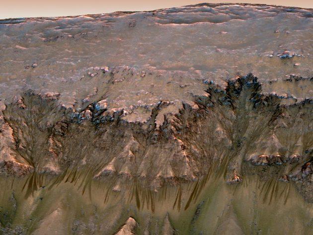 Blick auf einen Mars-Kraterrand und damit auch unter in den Untergrund der Marsoberfläche. Dunkle Rinnenstrukturen werden kontrovers auch als mögliche Austritte von Schmelz- und Untergrundwasser diskutiert (leicht gestauchte Ansicht). Copyright: NASA/JPL-Caltech/Univ. of Arizona